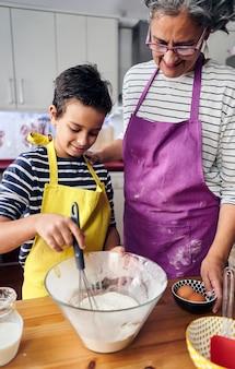 Madre caucasica che insegna a suo figlio come cucinare preparando gli ingredienti per fare una torta