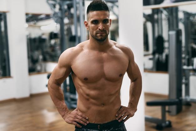 Uomo senza camicia muscolare caucasico con le mani sulle anche che posano in una palestra