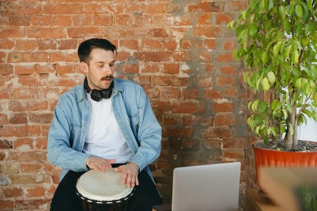 Musicista caucasico che suona il tamburo a mano durante il concerto online a casa isolato e messo in quarantena. utilizzo di fotocamera, laptop, streaming, registrazione di corsi. concetto di arte, supporto, musica, hobby, educazione.