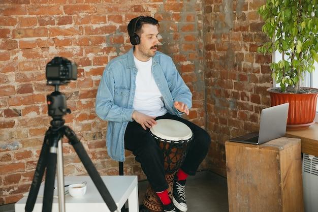 Musicista caucasico che suona il tamburo a mano durante il concerto online a casa isolato e messo in quarantena.
