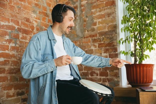 Musicista caucasico che suona il tamburo a mano durante il concerto online a casa