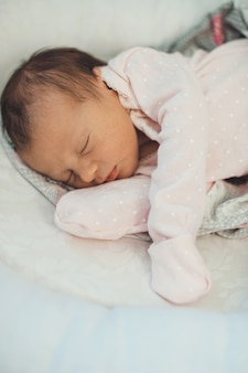 Ragazza neonata caucasica che dorme in vestiti dentellare che si trovano su una coperta bianca morbida