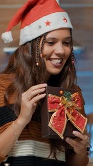Persona caucasica che mostra un regalo avvolto durante una videochiamata