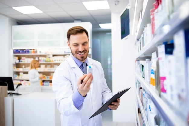 Farmacista caucasico che lavora in farmacia e controlla la data di scadenza dei farmaci.