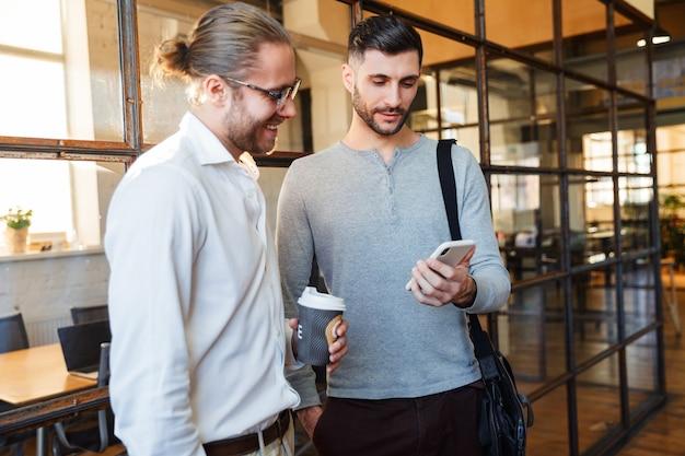 Colleghi caucasici contenti che parlano e usano il cellulare mentre si trovano in un ufficio moderno