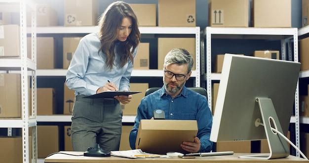 Lavoratrice caucasica della posta che porta scatola all'uomo che lavora al computer nell'ufficio di consegna. pacco di registrazione maschio e codice a barre di scansione con scanner.