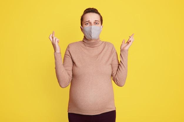 La donna incinta caucasica in maschera protettiva contro l'influenza e i virus che posano isolata sopra la parete gialla con le dita incrociate, essendo preoccupata, spera di essere la salute durante la pandemia.
