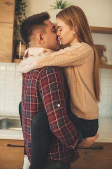 La ragazza dai capelli rossi caucasica con le lentiggini sta abbracciando il suo amante che ha momenti romantici insieme