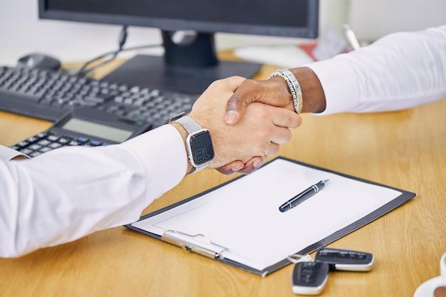 Venditore caucasico e cliente afro nero che agitano le mani congratulandosi a vicenda