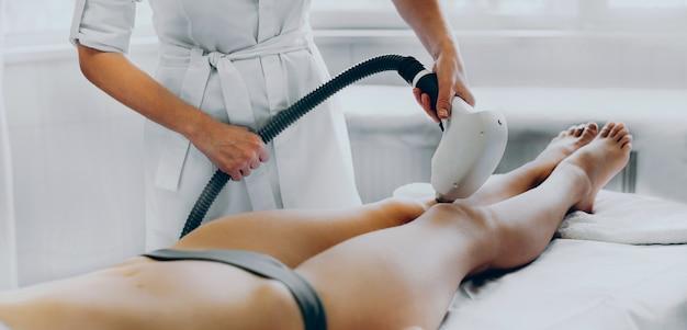 Il lavoratore del salone caucasico sta rimuovendo i capelli dalle gambe del cliente utilizzando un apparecchio moderno