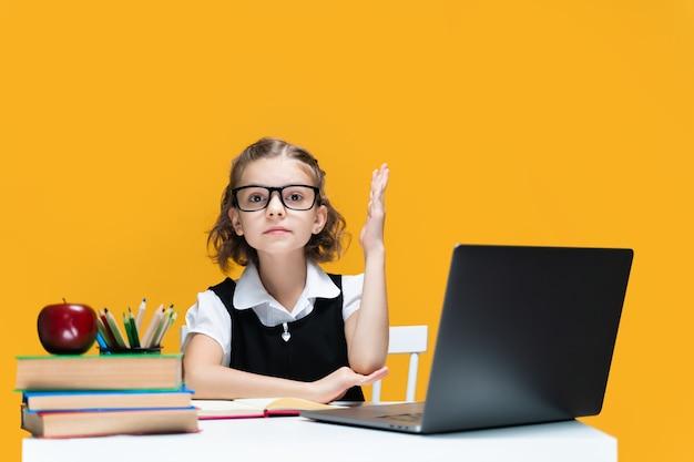 Scolara caucasica alzando la mano seduto al laptop durante la lezione online apprendimento scolastico distante
