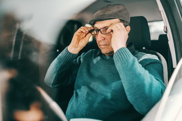 Uomo senior caucasico con il cappuccio sulla testa che mette gli occhiali mentre sedendosi in un'automobile