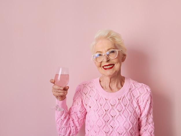 Donna anziana caucasica in maglione rosa cashmere che beve rosa su sfondo rosa