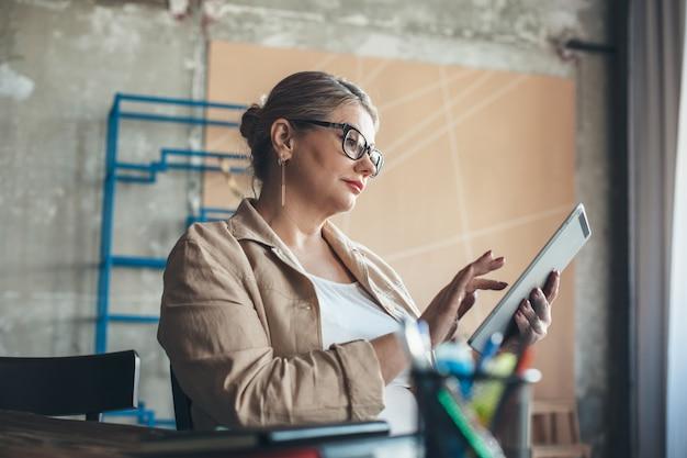 Donna senior caucasica con capelli biondi che lavora su un tablet da casa con gli occhiali da vista e utilizzando alcune cose da ufficio