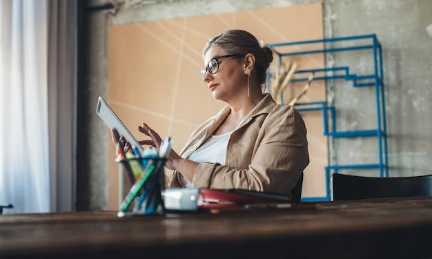 La donna senior caucasica con gli occhiali sta utilizzando un tablet durante un'intensa giornata di lavoro da casa