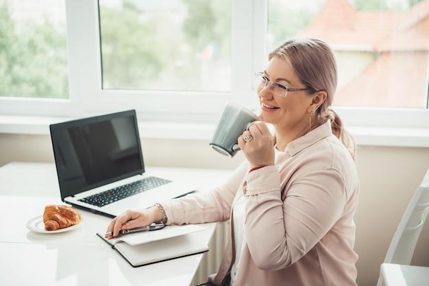 Donna maggiore caucasica che lavora al computer portatile da casa mentre beve il tè con croissant e sorriso