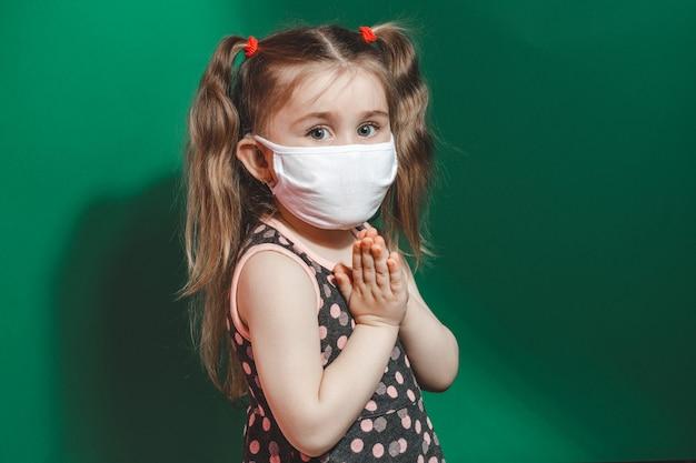 La bambina ammalata caucasica nella mascherina medica durante l'epidemia di coronavirus prega sul primo piano verde 2021 del fondo.