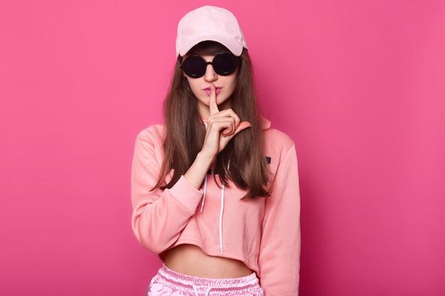 Adolescente snello giovane ragazza caucasica in felpa con cappuccio accorciata brillante in posa su roseo, tiene il dito davanti alla bocca, chiedendo silenzio. shhh, segreto.