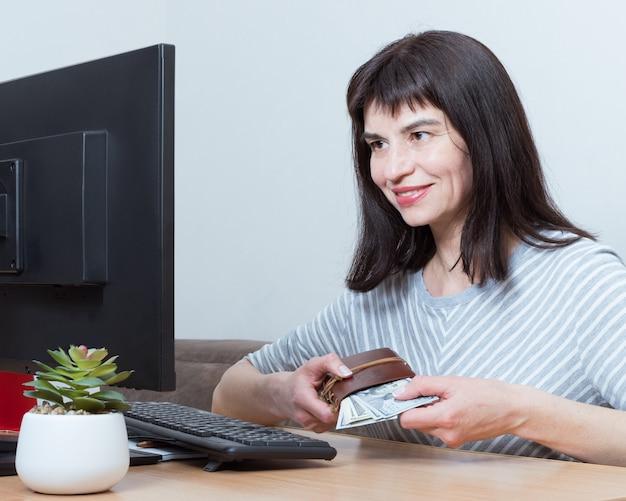 Donna sorridente caucasica seduta davanti al monitor e in possesso di contanti per gli acquisti online. lo shopping online a casa concetto. comprare regali per le feste