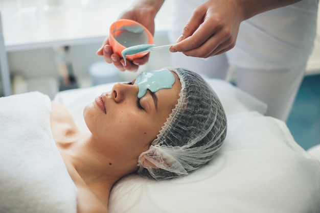 Il lavoratore caucasico della spa sta applicando una maschera speciale sul viso di un cliente utilizzando strumenti speciali