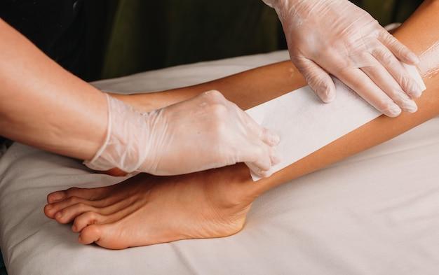 Il lavoratore caucasico della stazione termale sta avendo una sessione di ceretta sulle gambe con il suo cliente sdraiato sul divano