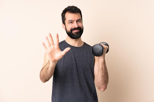 Uomo caucasico di sport con la barba che fa sollevamento pesi sopra fondo isolato contando cinque con le dita