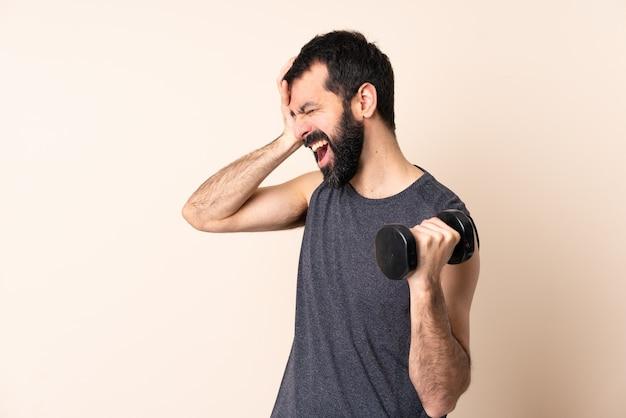 Uomo sportivo caucasico con la barba che fa sollevamento pesi su sfondo isolato stressato sopraffatto
