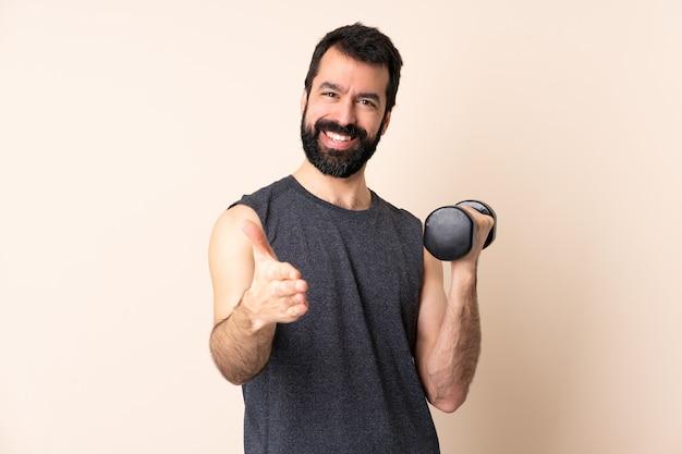 Uomo caucasico di sport con la barba che fa sollevamento pesi sopra le mani tremanti isolate per chiudere un buon affare