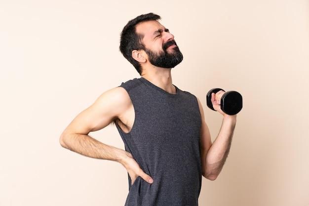 Uomo caucasico di sport con la barba che fa sollevamento pesi sulla sofferenza isolata dal mal di schiena per aver fatto uno sforzo