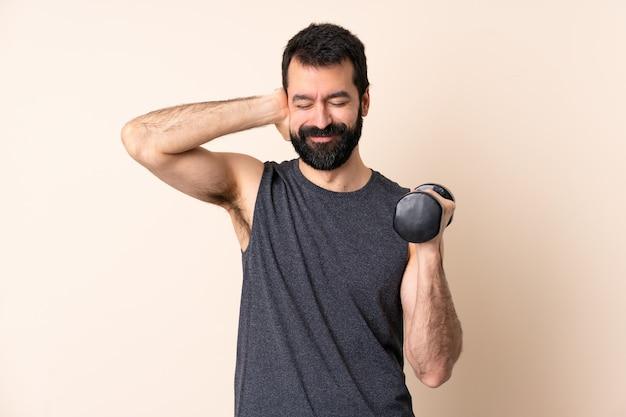 Uomo caucasico di sport con la barba che fa sollevamento pesi sopra la parete isolata frustrata e che copre le orecchie