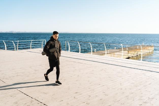 Sportivo caucasico 20s in abiti neri che indossa auricolari che camminano in riva al mare dopo l'allenamento mattutino