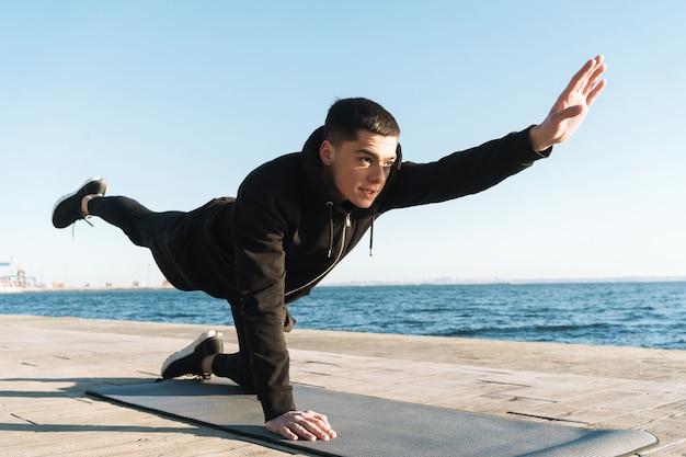 Sportivo caucasico 20s in tuta da ginnastica sdraiato sul tappetino fitness e facendo esercizio di plancia mentre si lavora in riva al mare al mattino