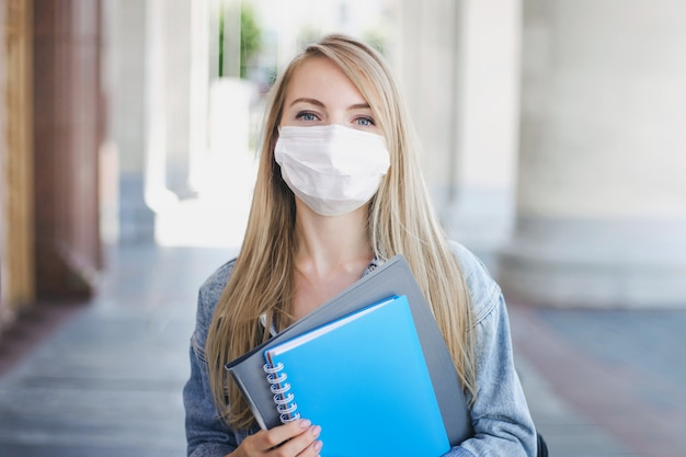 Ragazza caucasica dell'allievo che porta una mascherina medica