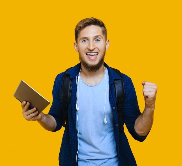 Studente caucasico con capelli rossi e bella barba è in possesso di un tablet e indossa una cartella