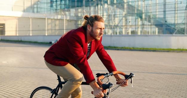 Ciclista maschio elegante caucasico in giacca casual rossa in sella a una bici in strada in città. uomo bello con earing avendo giro in bicicletta. edificio moderno in vetro sullo sfondo. paesaggio urbano. giorno soleggiato.