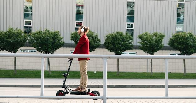 Giovane alla moda caucasico in cuffie che guidano scooter elettrico e in piedi ancora sulla strada in città. bello cavaliere maschio che ascolta la musica mentre va da qualche parte. gita in città.