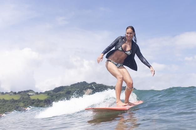Surfista caucasica sulla tavola da surf donna nell'oceano durante il surf surfer e ocean wave