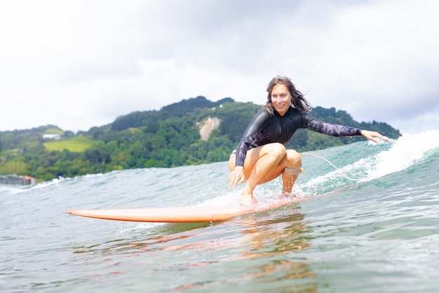 Surf caucasica donna sulla tavola da surf durante il surf. surfista e onda dell'oceano