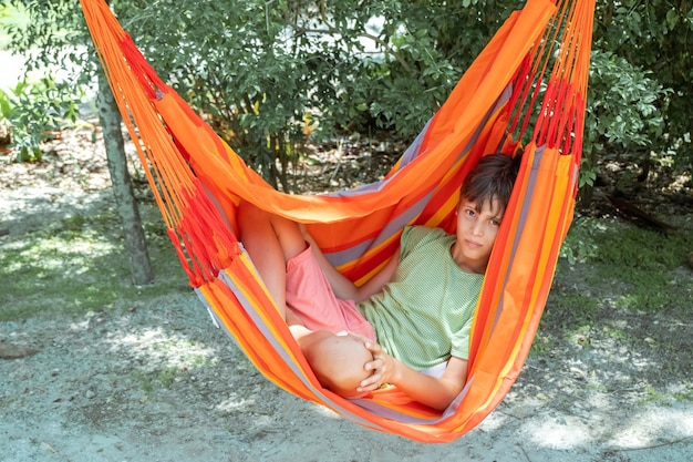 Ragazzo caucasico dell'adolescente che si rilassa in amaca arancione a strisce luminose tempo libero attivo estivo per i bambini