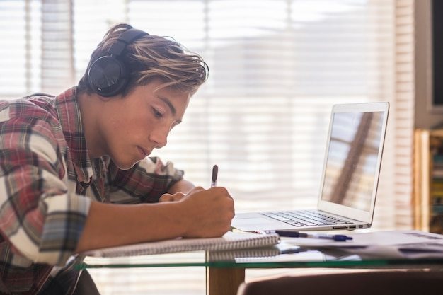 Adolescente caucasico indoor che fa i compiti sul tavolo a casa - ragazzo biondo che scrive e legge nel suo laptop o computer per ottenere ottimi punteggi