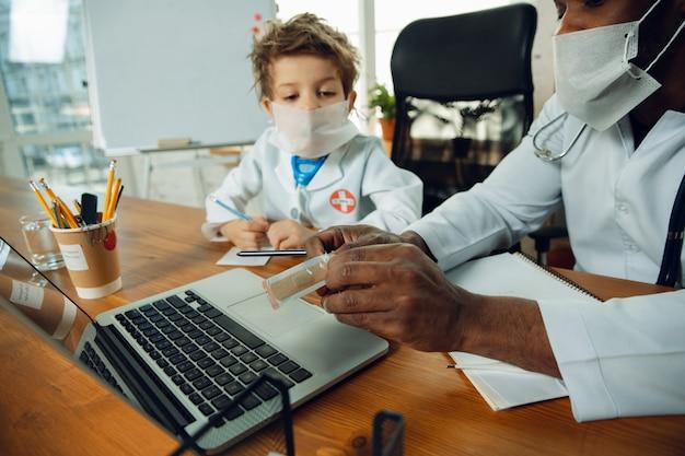 Adolescente caucasico come consulente medico, che dà raccomandazioni, cura. piccolo dottore durante la discussione, studiando con il collega più anziano. concetto di infanzia, emozioni umane, salute, medicina.