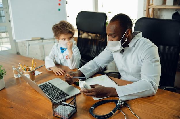 Adolescente caucasico come un medico che consulta, dà consigli, tratta. piccolo dottore durante la discussione, studiando con il collega più anziano. concetto di infanzia, emozioni umane, salute, medicina.