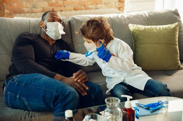 Adolescente caucasico come medico che consulta il paziente, dà consigli, tratta. piccolo dottore durante il controllo dei polmoni del suo paziente. concetto di infanzia, emozioni umane, salute, medicina.