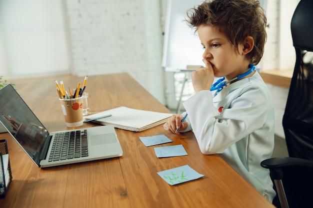 Adolescente caucasico come medico che consulta il paziente, dà consigli, tratta. piccolo dottore durante la prescrizione di farmaci per il paziente. concetto di infanzia, emozioni umane, salute, medicina.