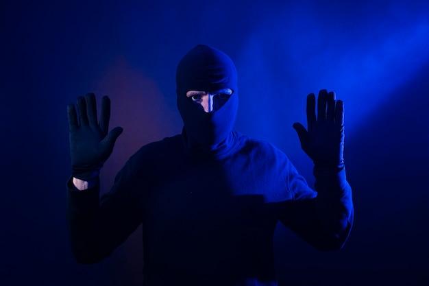 Ladro caucasico con le mani in alto. include le luci della polizia.