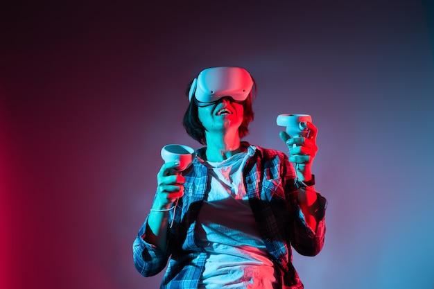 Donna caucasica 35-40 anni di azione nel casco di realtà virtuale. occhiali vr, concetto di tecnologia alla luce al neon.