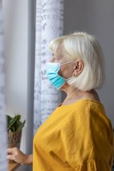 Donna caucasica di 50 anni in una maschera medica protettiva che guarda fuori dalla finestra mentre era seduta a casa o in ospedale in carrozza durante la pandemia di coronavirus.