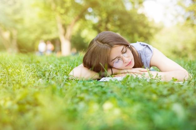 Donna caucasica addormentata mentre legge un libro sul prato verde estivo summer