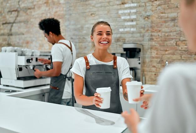 Barista della donna caucasica che dà le tazze di caffè, latte o cappuccino al cliente alla caffetteria.