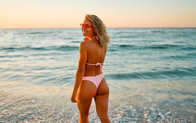 La donna caucasica in costume da bagno bikini passeggia sulla spiaggia all'alba godendosi il suono delle onde.
